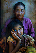 Mother and daughter rest after working with the organic coffee bushes at Bolaven Coffee, Laos.