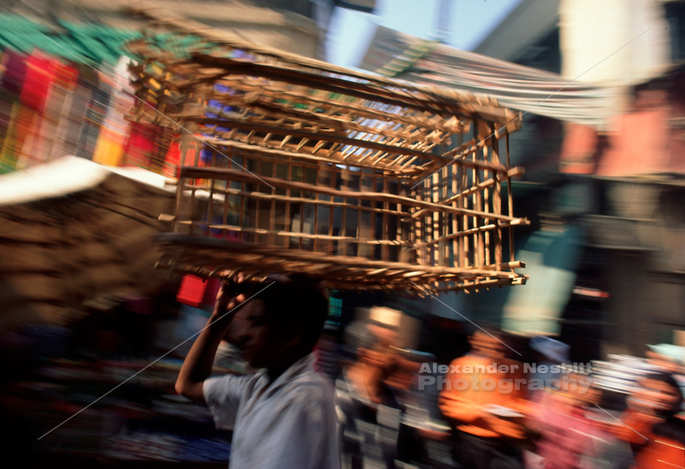 Egypt, 2000 - A delivery boy bikes through crowded Cairo market while balancing a wooden cage on his head.