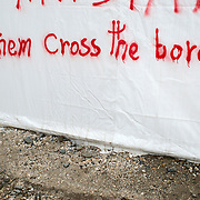 Greece with Doctors of the World (Medecins du monde). Idomeni, border crossing Greece and Macedonia (Fyrom). Refugees come on buses from Athens (costs 20 euros). Graffiti on a UNHCR tent saying 'Let them cross the border'.