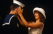 A married couple ready themselves for a formal Buckingham Palace garden party in after sunshine. The lady and man have been invited to take tea with and meet the Queen along with many hundreds more in London England. They are Mr and Mrs Johnson and he is a Flag officer junior rating serving in Britain's Royal Navy. His wife adjusts his Navy cap (denoting his ship's name) to make sure it's straightened and presentable for Her Majesty. It is a proud day for her husband and his spouse, when the achievements of his military career are recognized by his Sovereign. The Queens' garden parties are held ever summer, allowing ordinary men and women from diverse members of society the chance to walk the Palace grounds and meet others from all walks of life. Some may be from the armed services and others , merely known for their charitable work or individual merit.