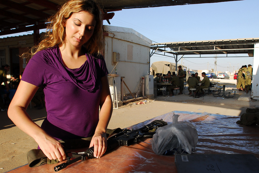 An IDF woman reserve soldier receives a gun as she arrives at her training base in the Negev Desert, South Israel on September 10, 2008. Following their active service, women, like men, are in theory required to serve up to one month annually in reserve duty. However, in practice only some women, mostly in combat roles, get called for active reserve duty, and only for a few years following their active service, with many exit points (e.g., pregnancy).