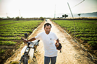 Touneh Du, a Chu Ru ethnic minority farmer in Lam Dong province, central Vietnam, leans on his motorbike on his farmlands. Du receives roughly US$150 each year from PES programs in Lam Dong province.
