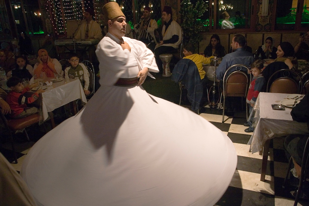 The Melaweieh dance performance in a Restaurant in Damascus (Syria). This is an religious, mystic and spiritual dance. The dancer turns on himself (spins) leaning to one side or to the front 99 times to reach religious ecstasy. The Melaweieh dancer wears broad white clothes and a typical conical hat. <br /> Un hombre ejecuta el baile tradicional sirio en un restaurante de Damasco (Siria). El bailar&iacute;n ejecuta 99 giros a toda velocidad sobre si mismo, llegando hacia el final a un estado de comunicaci&oacute;n m&iacute;stica con Dios, seg&uacute;n cuenta la tradici&oacute;n.<br /> Ejecuci&oacute;n del baile tradicional sirio en el sal&oacute;n de un restaurante en Damasco. El bailar&iacute;n ejecuta 99 giros sobre si mismo, llegando hacia el final a un estado de comunicaci&oacute;n m&iacute;stica con Dios, seg&uacute;n cuenta la tradici&oacute;n.