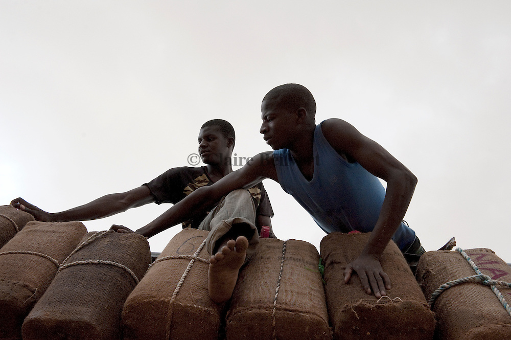 Two young african migrants hanging cans full of water on a truck. They are preparing their travel to Dirkou, Niger, not far from the libyan border.