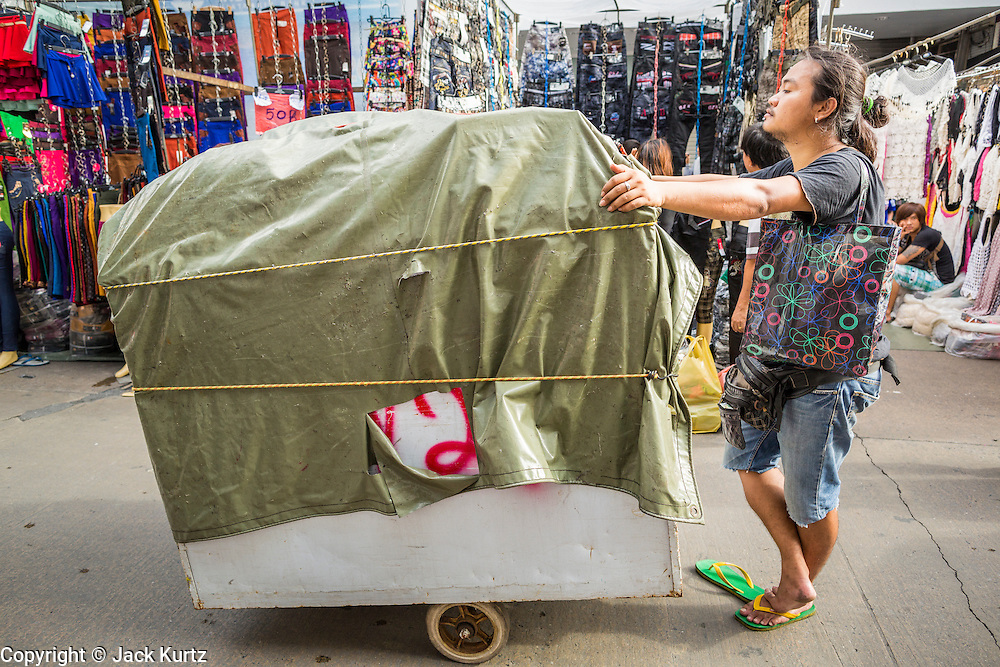 06 JUNE 2013 - BANGKOK, THAILAND:     A porter takes a load of clothing into Bobae Market in Bangkok. Bobae Market is a 30 year old market famous for fashion wholesale and is now very popular with exporters from around the world. Bobae Tower is next to the market and  advertises itself as having 1,300 stalls under one roof and claims to be the largest garment wholesale center in Thailand.       PHOTO BY JACK KURTZ
