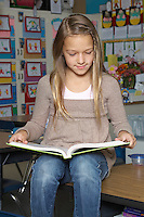 School girl reading book on desk in classroom