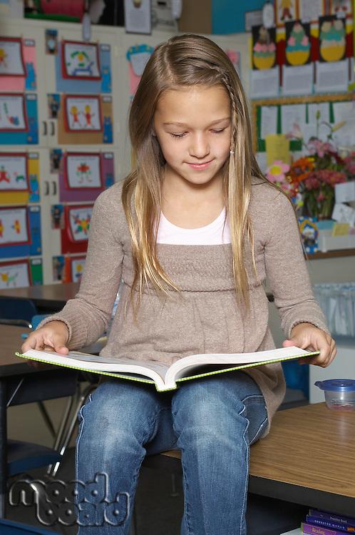 School girl reading book on desk in classroom