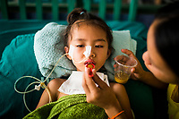 Namfon, aged 6, suffers from Japanese Encephalitis at a hospital in Vientiane, Laos. Her mother tries to feed her small amounts of solid food each day.