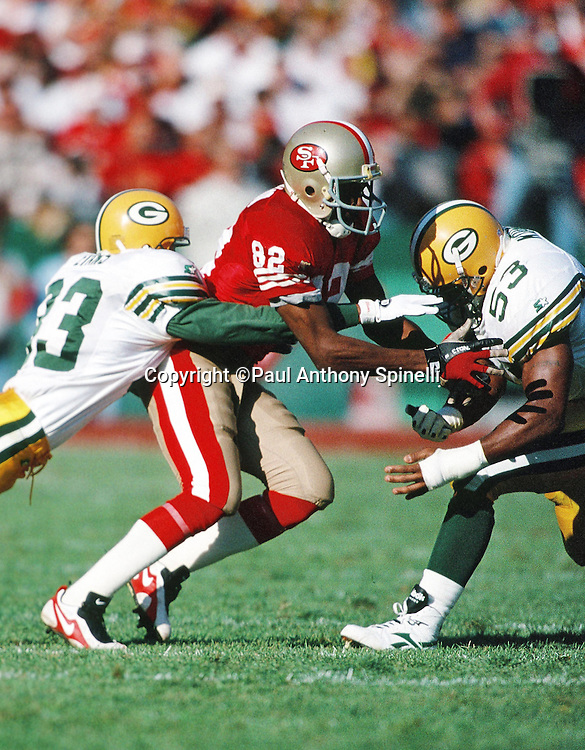 Green Bay Packers cornerback Doug Evans (33) and Packers linebacker George Koonce (53) hit San Francisco 49ers wide receiver John Taylor (82) during the NFL NFC Divisional Playoff football game against the San Francisco 49ers on Jan. 6, 1996 in San Francisco. The Packers won the game 27-17. (©Paul Anthony Spinelli)