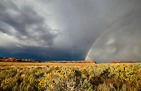 A rainbow and storm clouds over the desert of Southeast Utah, near Canyonlands National Park, USA.