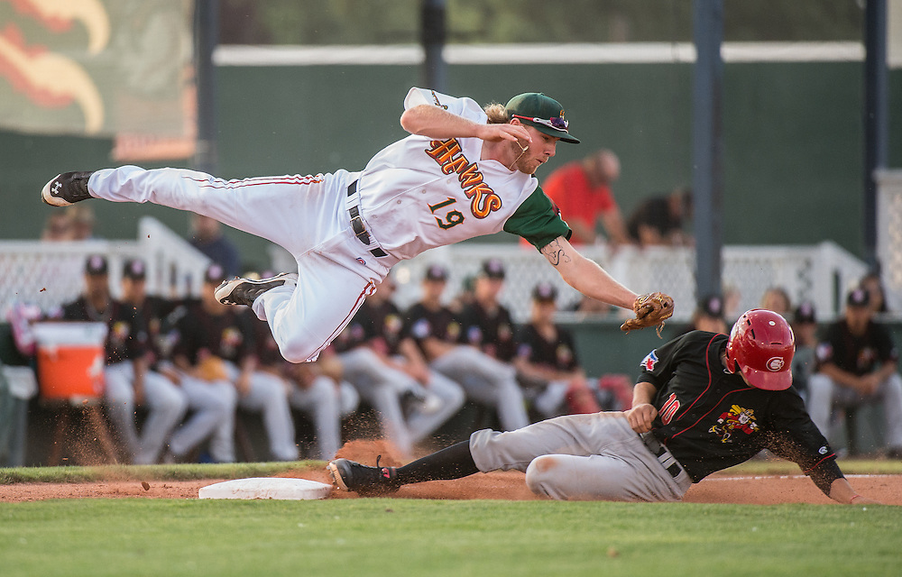 The Vancouver Canadians Tim Locastro steals third under the tag of Boise Hawks third baseman, Jesse Hodges during a game in Boise, Idaho.