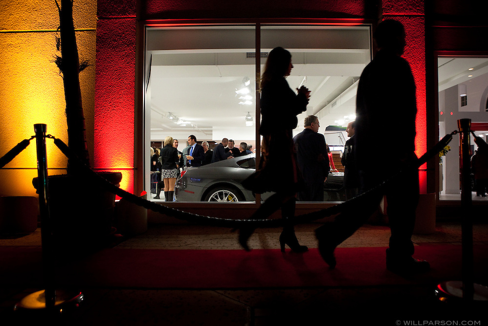 Visitors walk down a red carpet toward the entrance to the Ferrari showroom during their grand opening.