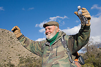 Senior male hiker raising arms and smiling