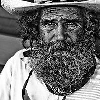 This Caliornia Farmworker photo is full of details. From his weathered face to his worn hat; from the sunglasses hanging around his neck to the rolling tobacco in his top pocket to the print neck scarf; from his graying, scraggly hair and beard to those eyes that reveal a thousand stories.