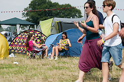 © Licensed to London News Pictures. 18/07/2014. Southwold, UK.   Festival goers relax in the hot sun next to their tents at  Latitude Festival 2014 Day 1. Today is expected to be the hottest day of the year with temperatures forecast to reach 32 degrees centigrade.   Latitude is an British annual music festival.  Photo credit : Richard Isaac/LNP