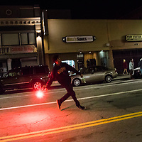NOVEMBER 9, 2016 - OAKLAND, CA: An Anti-Trump protester lobs a flare at a line of Police officers, after protesters take the streets to express their sentiments over the victory of Donald Trump in the 2016 Presidential Election, in Oakland, California on November 9, 2016. (Photo by Philip Pacheco)