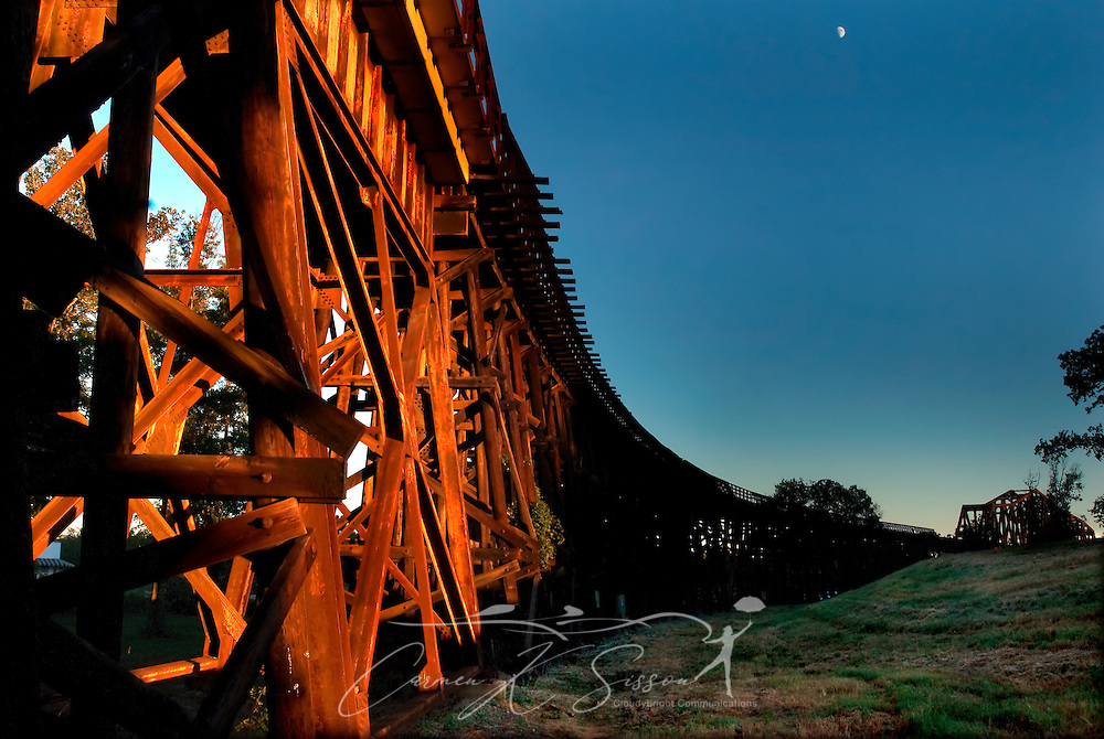 The moon rises above the M&O Railroad trestle on Oct. 20, 2007 in Northport, Ala. The wooden and steel truss bridge was build in 1898 for the Mobile and Ohio Railroad. At 135 feet high and 3,600 feet long, it is considered by many to be the country's longest wooden trestle still in use. (Photo by Carmen K. Sisson/Cloudybright)
