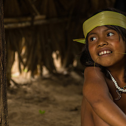 A young girl of the Huaorani tribe is sitting and laughing on the floor of the communal area, Yasuni Reserve, Ecuador.