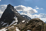 Two female hikers are resting on a glacier polished rock and the peak of the Rothorn close to the lake Geisspfadsee, Landschaftspark Binntal, Valais, Switzerland