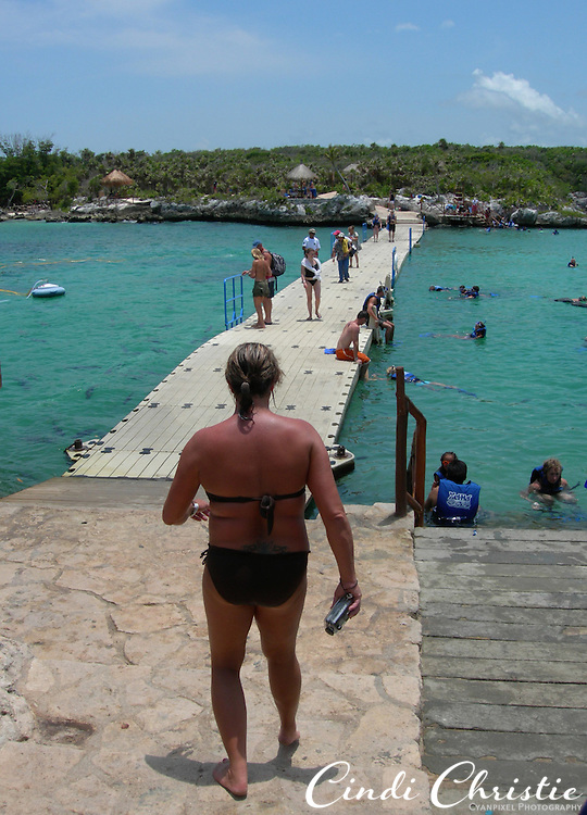 A woman prepares to step onto the wiggly, wobbly floating bridge where the sea meets the inlet at Xel-Ha Lagoon water park and ecology center along the Riviera Maya south of Cancun, Mexico, on May 24, 2007. (© 2007 Cindi Christie)