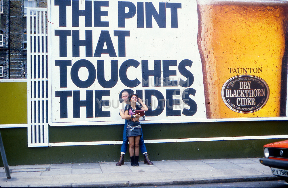 Gavin and Kelly in front of Blackthorn billboard, UK, 1980s.