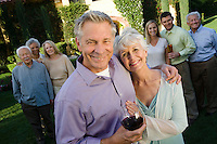 Senior couple celebrating with family and friends in garden