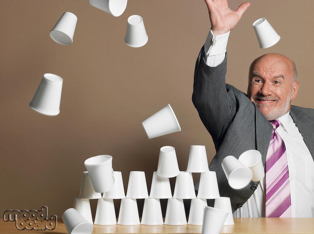 Businessman knocking down pyramid of plastic cups