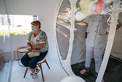 A woman visits her mother in a bubble at Fondation Shadet Vercoustre nursing home as a caregiver waits in a airlock on May 27, 2020 in Bourbourg near Gravelines, France, where a double entry bubble has been installed to allow visits without risk of contamination, as part of a prophylactic measure against the spread of the Covid-19 disease caused by the novel coronavirus. Relatives and residents each enter the tent through a different entrance to find themselves in the same room, separated by a transparent plastic canvas. These bubbles were originally designed for tourism by the company. Photo by Julie Sebadelha/ABACAPRESS.COM