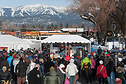 The crowd watching Montana musician Jack Gladstone on the stage at the Love Not Hate gathering in Whitefish, MT, with Whitefish Mountain ski resort in the distance.