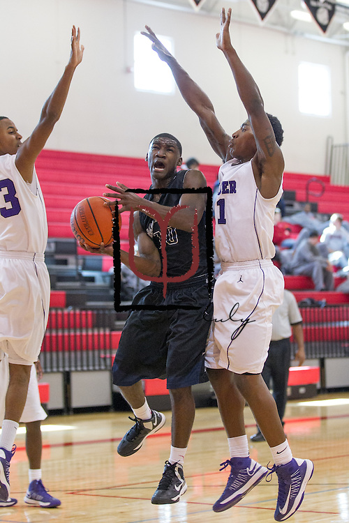 Shoemaker's Qwoy Blunt attempts to shoot between Cedar Ridge's Jalil Francois and De'Andre Davis during the Leander ISD Tournament Friday.  The Raiders beat the Grey Wolves 58-37 at Vista Ridge Gym.