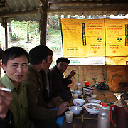 Men drink and smoke at the Lung Khau Nhin Market. Vietnam. Lung Khau Nhin Market is rural tribal market hiding itself amongst the mountains and forests of the far north Vietnam about 10 km from the border with China. The market plays an important role for the local ethnic people, Flower Hmong, Black Zao, Zay, and very small ethnic groups  Pa Zi, Tou Zi, Tou Lao. Tourist trips to the market run from Sapa and Lao Cai every week. Lung Khau Nhin Market, Vietnam.15th March 2012. Photo Tim Clayton