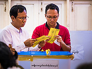 08 NOVEMBER 2015 - YANGON, MYANMAR: Men review their ballots before putting them in a ballot box in a polling place in central Yangon. The citizens of Myanmar went to the polls Sunday to vote in the most democratic elections since 1990. The National League for Democracy, (NLD) the party of Aung San Suu Kyi is widely expected to get the most votes in the election, but it is not certain if they will get enough votes to secure an outright victory. The polls opened at 6AM. In Yangon, some voters started lining up at 4AM and lines were reported to long in many polling stations in Myanmar's largest city.      PHOTO BY JACK KURTZ