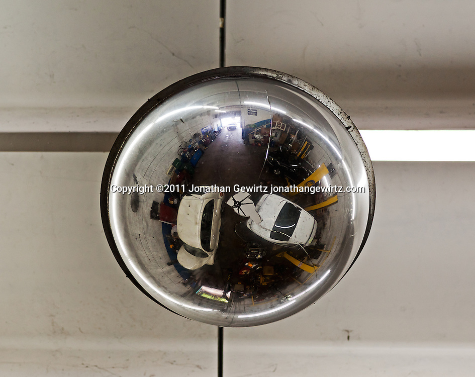 The interior of an automotive repair shop as reflected from a chromed planter on the ceiling. WATERMARKS WILL NOT APPEAR ON PRINTS OR LICENSED IMAGES.