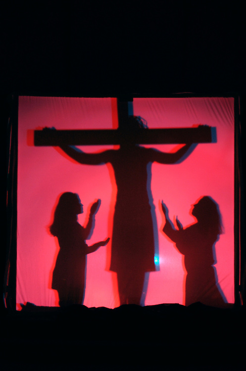 JESUS DIES ON CROSS -- High school students perform shadow stations of the cross. (Photo by Sam Lucero)