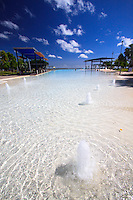 A shallow area with small water fountains and statues to climb on provides a great place for young children and babies to play at the Cairns Esplanade Lagoon on the foreshore in this far north Queensland city, Australia.