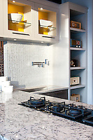A contemporary kitchen in Urbana Kitchens showroom in Victoria, BC features bold yellow insets on the upper glass cabinets, white Cambria quartz counters and a metal-backed glass tile backsplash.