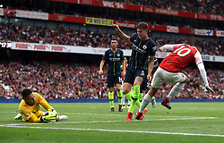 Manchester City goalkeeper Ederson (left) makes a save from Arsenal's Mesut Ozil (right)