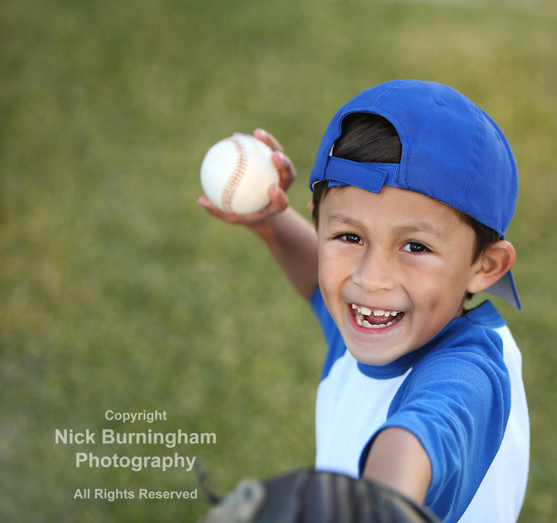 Happy smiling young latino boy dressed in blue baseball sleeves with cap, glove and ball