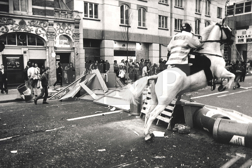 © Licensed to London News Pictures. 25/03/2020. London, UK. In this image from March 31st 1990 a mounted police officer jumps his horse over a barricade on Upper St Martin's Lane during the London poll tax riots. The protest on the last day of March in 1990 started peacefully when thousands gathered in a south London park to demonstrate against Margaret Thatcher's Government's introduction of the Community Charge - commonly known as the poll tax. Marchers walked to Whitehall and Trafalgar Square where violence broke out with the trouble spreading up through Charring Cross Road and on to the West End. Police estimated that 200,000 people had joined the protest and 339 were arrested. The hated tax was eventually replaced by the Council Tax under John Major's government in 1992.  Photo credit: Peter Macdiarmid/LNP