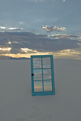 Mirrored window frame reflecting the sky at sunset on white sand dune in New Mexico