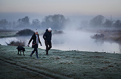 © Licensed to London News Pictures. 17/01/2017. Ripley, UK.  near Ripley. A couple walk their dog by the River Wey near Ripley at first light. Cold temperatures are set to continue for most of the United Kingdom. Photo credit: Peter Macdiarmid/LNP