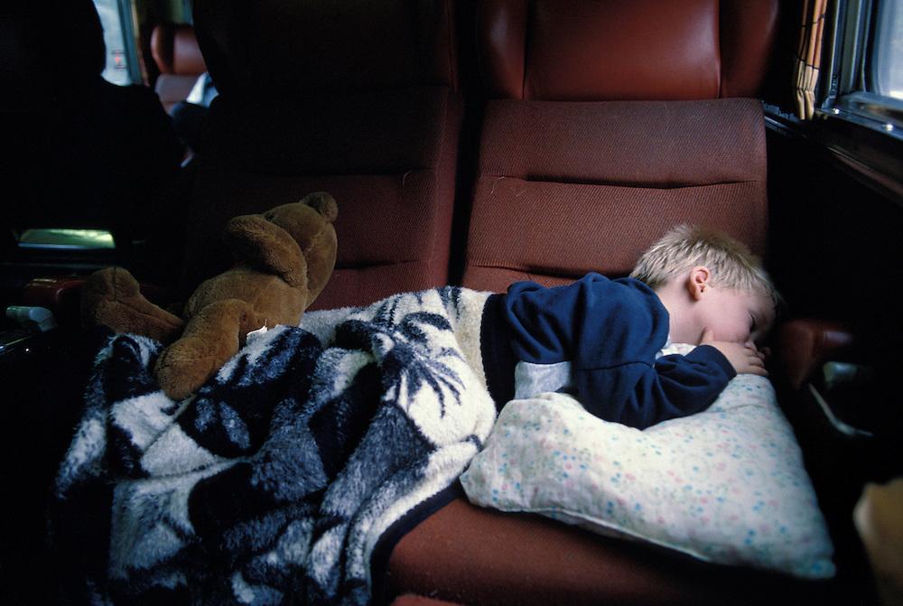 Canada, Ontario, Three-year-old John Power sleeps on chairs in VIA Rail passenger train in eastern Ontario