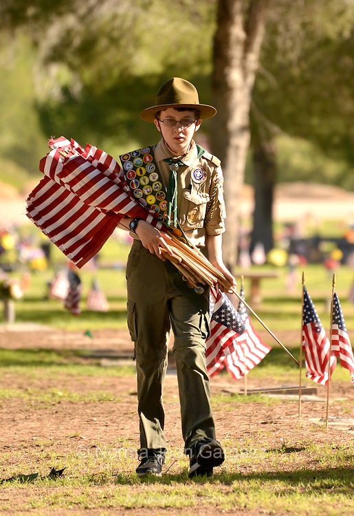 """Boy Scout, Ray Langlais, 13, places flags on May 25, 2013 at the graves of deceased U.S. military veterans in preparation for Monday's Memorial Day services in Tucson, Arizona, USA.  Langlais says that he helps place the flags to """"help my country""""."""