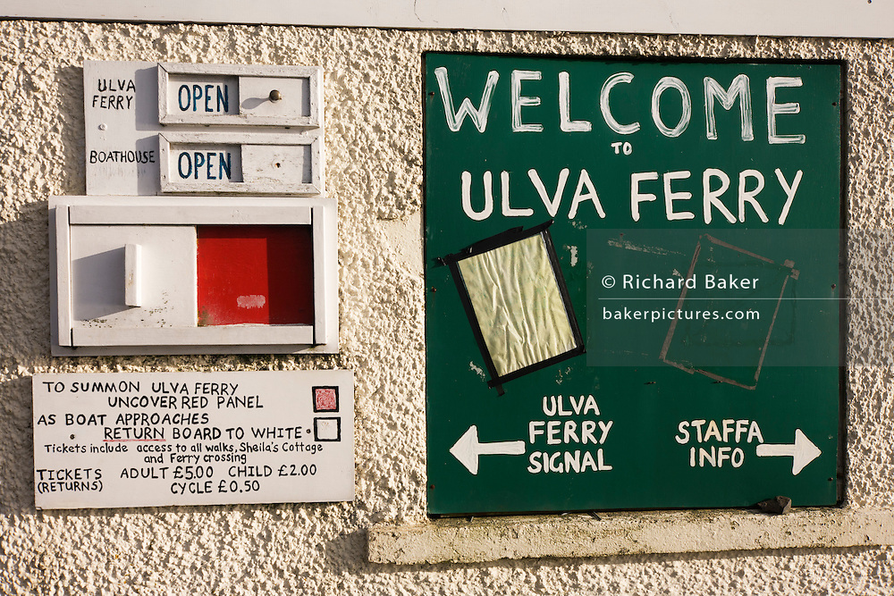 "Ferry signs foer the Ulva ferry, Isle of Mull, Scotland. Ulva is open from Easter to October; the ferry which takes foot passengers and bicycles runs Monday to Friday 9 - 5. The crossing only takes a couple of minutes and is on demand; summon the ferry by uncovering the red panel on the pier but don't forget to cover it again as the boat approaches. The island is closed on Saturdays but opens on Sundays from June to the end of August. Ulva is a privately owned island with a thriving population of approximately 16 people who are involved variously in traditional sheep and cattle farming, fish farming, oyster farming and tourism. There are no tarmac roads on Ulva, so the main form of transport is quad bikes used by all inhabitants, young and old. Ulva is from the Viking ""Ullamhdha"", or 'Nobody Home'. They named the island 'Ullfur', their word for 'Wolf Island'. ."