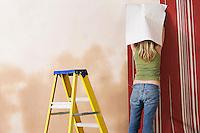 Woman hanging wallpaper back view