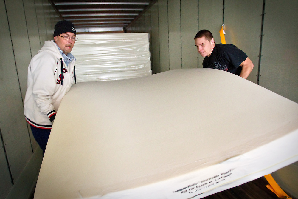 Jeremy Rejniak, right, and Philip Rich, manager of the Sandman Transitional Housing for St. Vincent de Paul, carry one of the 10 new mattresses that were donated by Tempur-Pedic to replace the 15 and 20-year-old mattresses at the housing complex.