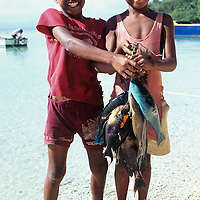 Fiji Islands, Yanuca Island, native boy islanders with fresh reef fish catch