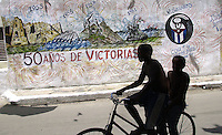 "Two unidentified boys riding a bike in front of a revolutionary mural painted for a revolutionary celebration, Friday July 25, 2003 in Havana, Cuba. Tomorrow, July 26, Fidel Castro, Cuban President, will celebrate the 50th anniversary of the attack he organized on the military barrack in Santiago de Cuba, about 900 km at east from Havana. Writing in Spanish reads: ""50 years of victory"". (AP Photo/Cristobal Herrera)"