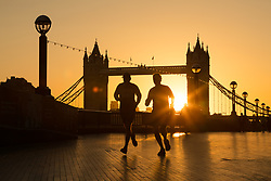 © Licensed to London News Pictures. 03/09/2017. LONDON, UK.  Morning commuters and joggers walk along the south bank during a golden sunrise this morning behind Tower Bridge on the River Thames, as the capital wakes up to a chilly and clear autumn morning. Photo credit: Vickie Flores/LNP