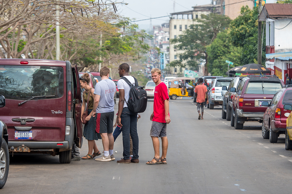A group of young people load into a car on the streets of Monrovia, Liberia